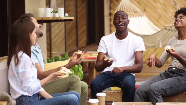 multikulturelle glückliche freunde lachen pizza essen im restaurant im freien - teenage friends sharing food stock-videos und b-roll-filmmaterial