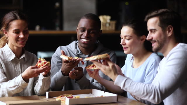 Multicultural happy friends talking laughing sharing takeaway pizza meal together