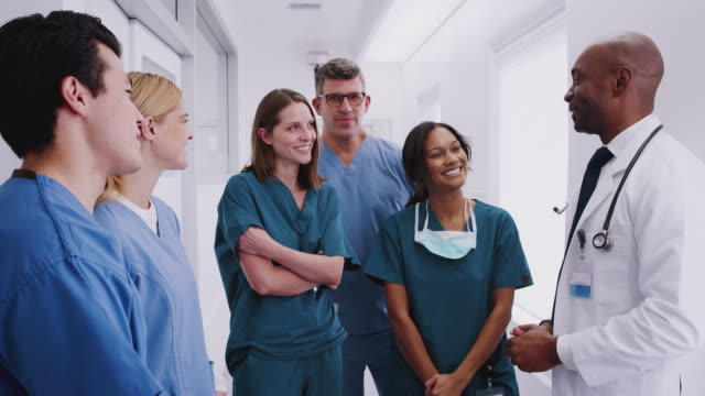 Multi-Cultural Medical Team Having Meeting In Hospital Corridor