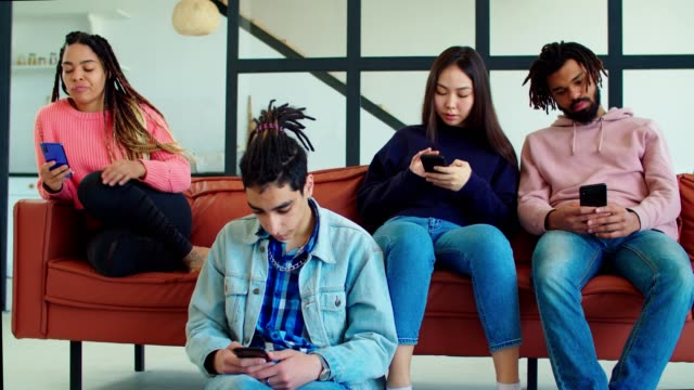 Multicultural smartphone addicted friends indoors