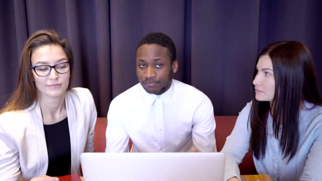 Multiethical team Novice businessmen talking while sitting at table with laptop in restaurant. African man