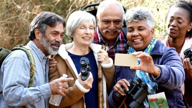vídeos de stock e filmes b-roll de multi-ethnic, active senior adult friends hiking in wooded forest area. - atividade recreativa