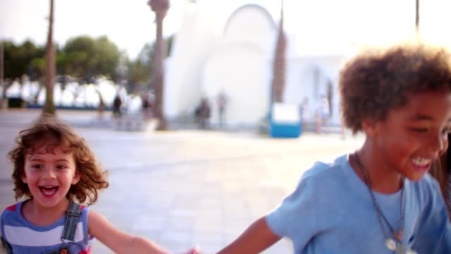 Multi-ethnic adopted family children on summer holidays running holding hands video