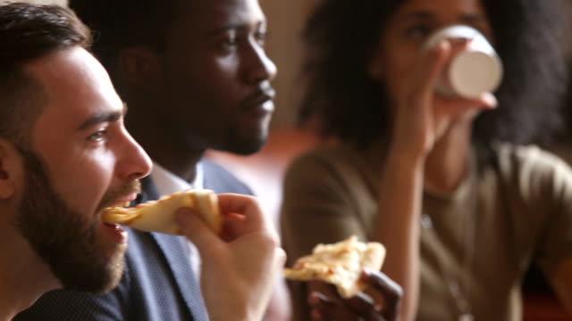 vídeos de stock, filmes e b-roll de amigos de preto e brancos multi-étnica comendo pizza na reunião dentro de casa - comida feita em casa