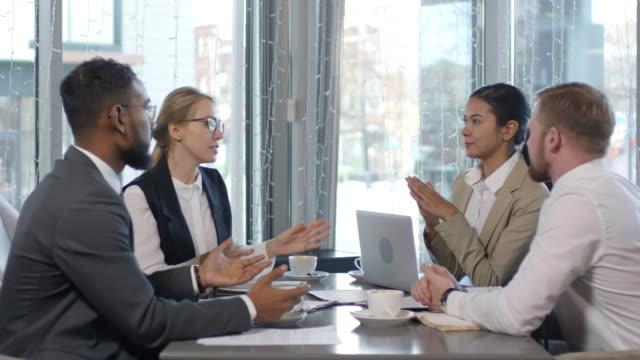 multi-ethnic business team brainstorming on coffee break in cafe - debate стоковые видео и кадры b-roll