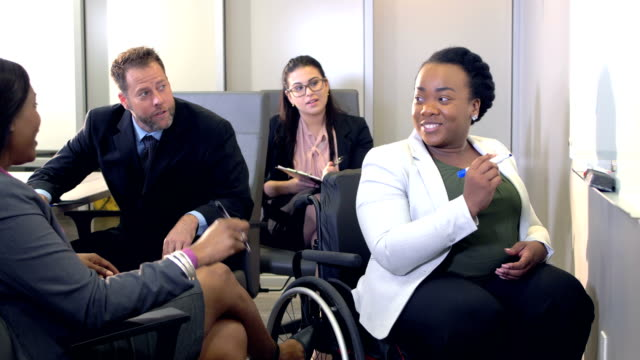 Multi-ethnic business team meeting, woman in wheelchair A multi-ethnic group of four business people together in an office board room, having a business meeting.  An African-American woman sitting in a wheelchair is writing on a white board. She has spina bifida. Another woman is leading the discussion. employee engagement stock videos & royalty-free footage