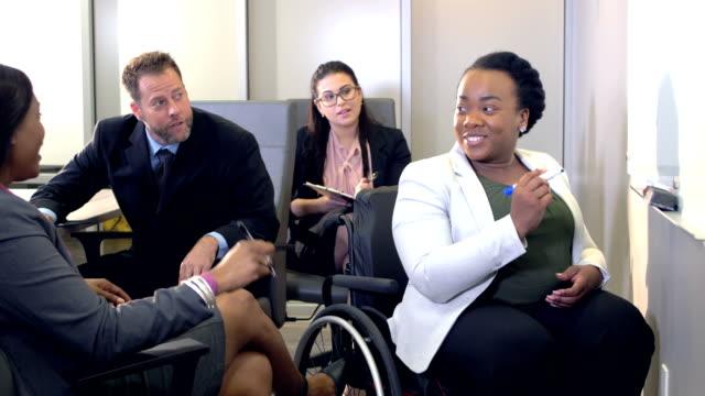 vídeos de stock e filmes b-roll de multi-ethnic business team meeting, woman in wheelchair - envolvimento dos funcionários