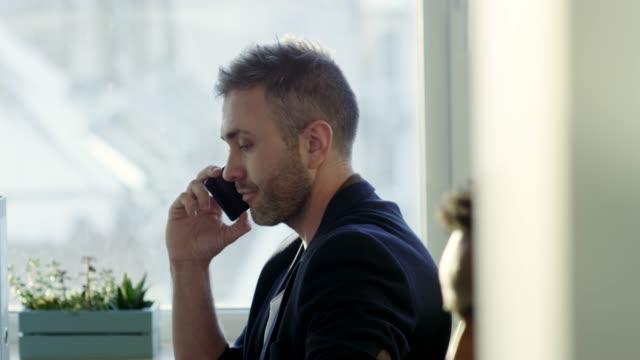 multi-ethnic businessmen speaking on phones at office desk - call center стоковые видео и кадры b-roll