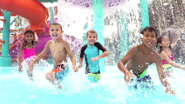 Multi-ethnic children at water park playing, splashing