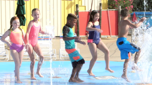 Multi-ethnic children at water park playing