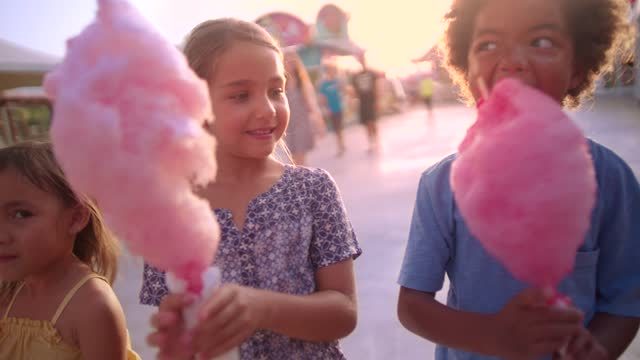 Multi-ethnic children eating cotton candy at amusement park Multi-ethnic adopted family children eating cotton candy at funfair on summer holidays cotton candy stock videos & royalty-free footage