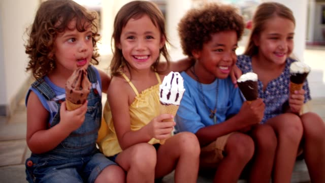 Multi-ethnic children eating ice-cream sitting on step outdoors in summer Multi-ethnic young best friends kids eating ice-cream together on summer holidays sitting on step outdoors ice cream stock videos & royalty-free footage