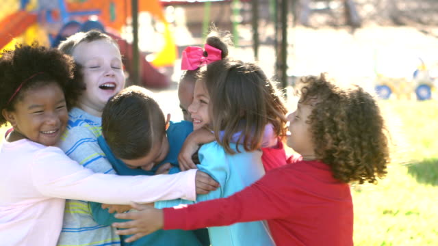 multi-ethnic children hugging on playground - children video stock e b–roll
