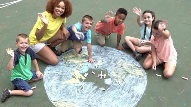 multietniska barn att göra krita ritning av jorden - samhörighet bildbanksvideor och videomaterial från bakom kulisserna