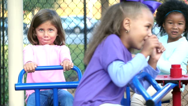 Multi-ethnic children on merry-go-round making faces video