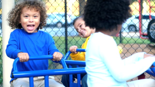Multi-ethnic children on playground merry-go-round A group of five multi-ethnic children, 5 to 6 years old, playing on a playground. They are spinning on a merry-go-round. child care stock videos & royalty-free footage