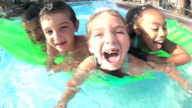 stockvideo's en b-roll-footage met multi-etnische kinderen op zwembad vlot glimlachend op camera - swimmingpool kids