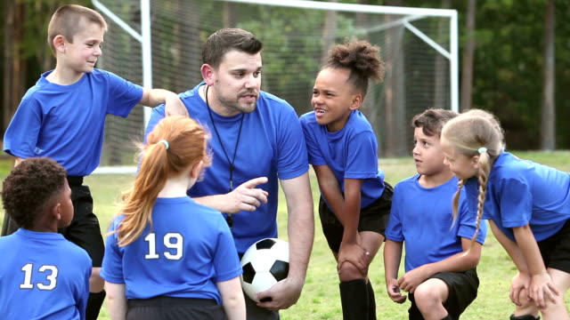 Multi-ethnic children on soccer team listening to coach video