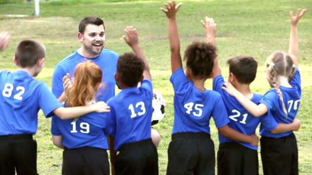 Multi-ethnic children on soccer team with coach video