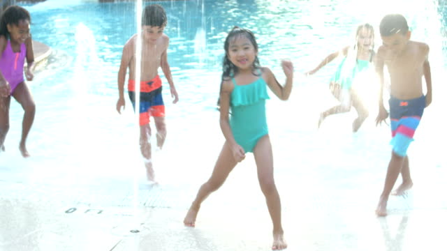 Multi-ethnic children playing at water park in fountains