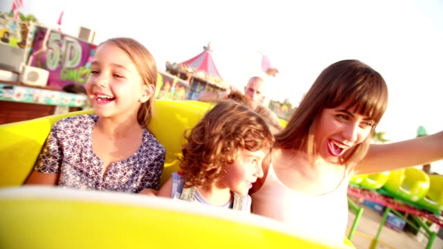 multi-ethnic children riding roller coaster ride at amusement park - luna park video stock e b–roll