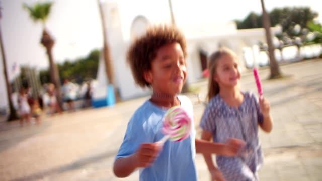 多族裔兒童一起在戶外捧著五顏六色的糖果 - 波板糖 個影片檔及 b 捲影像