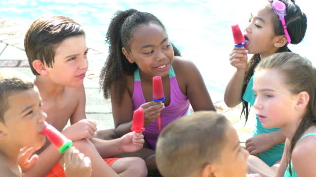 Multi-ethnic children sitting in circle eating popsicles