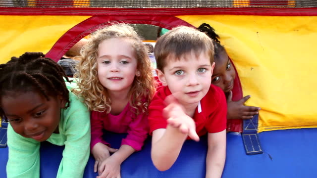 Multi-ethnic children sticking heads out bouncy castle video