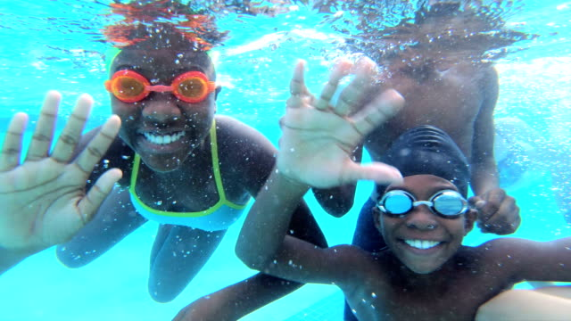 Multi-ethnic children underwater waving at camera A multi-ethnic group of six children, 10 to 12 years old, having fun swimming underwater, smiling and waving at the camera. swimming stock videos & royalty-free footage