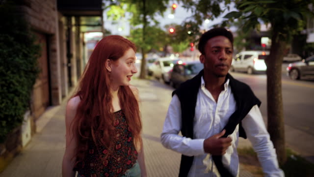 multi-ethnic couple flirting on the street at night - date night stock videos & royalty-free footage