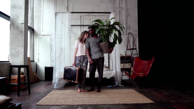 Multiethnic couple gather in travel. Woman holds suitcase, man holds plant. Boy and girl kisses and goes away video