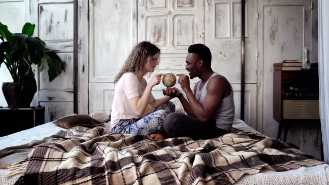 Multiethnic couple in pajamas sitting on the bed and twist the globe, choose the destination to traveling together video