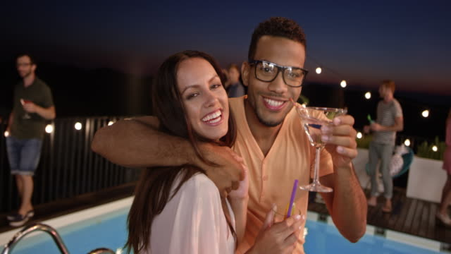 Multiethnic couple posing for a smartphone video at a party by the pool at night Wide handheld shot of a multiethnic couple posing for a smartphone video their friend is making at a party by the pool at night. Shot in Slovenia. pool party stock videos & royalty-free footage