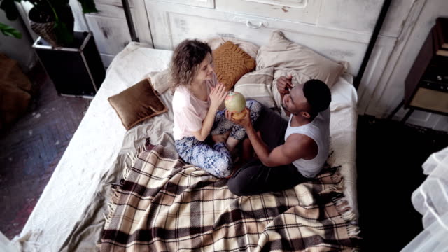 Multiethnic couple sit on the bed and twist the globe. Man and woman pick the destination to travel, hug and kiss video