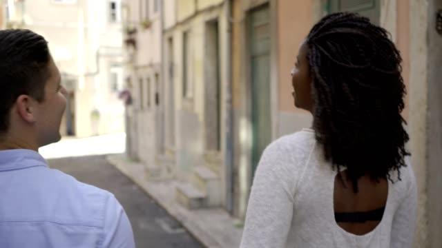 multietniskt par som går i gamla europeiska staden - människorygg bildbanksvideor och videomaterial från bakom kulisserna