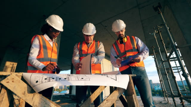 Multiethnic engineers, architects discussing construction plan. Engineers work with a blueprint on a table on a construction site.
