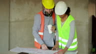 istock Multi-ethnic engineers discussing over blueprint at construction site 1180173560