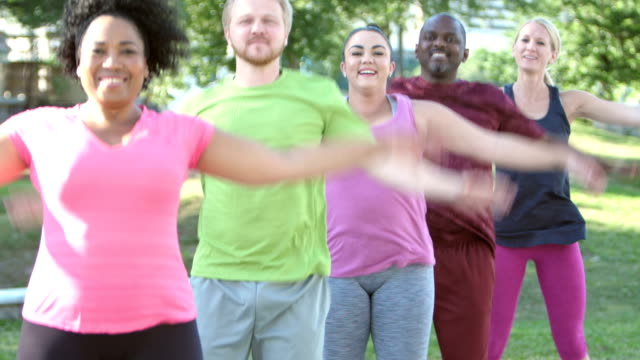 Multi-ethnic exercise class, jumping jacks in park video