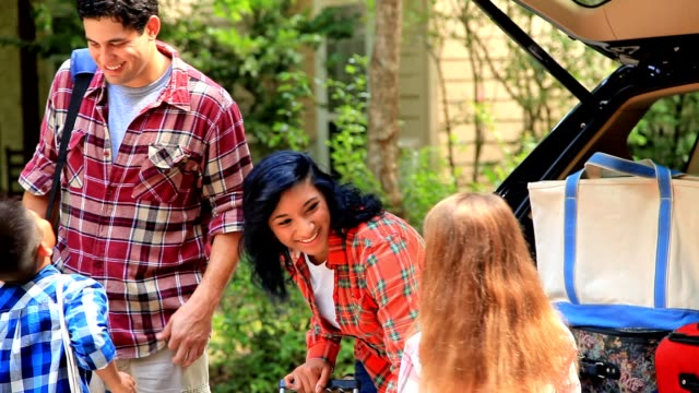 Voiture de pack familial multiethnique pour voyage de vacances ou de la route. - Vidéo