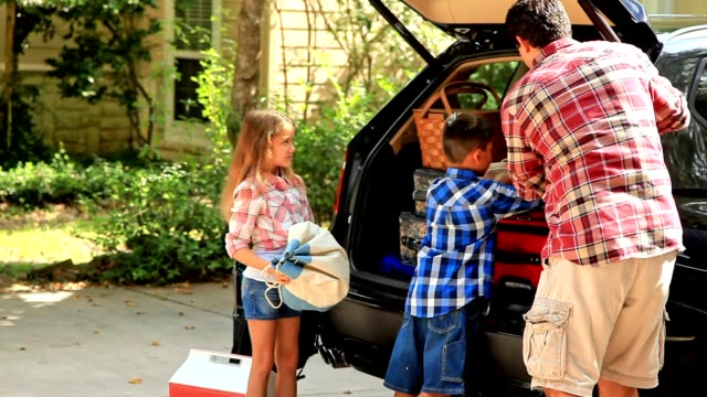 Video Multi-ethnic family pack car for vacation or road trip.