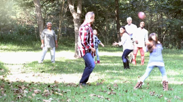 multi-ethnic family playing football in backyard at thanksgiving. - termine sportivo video stock e b–roll