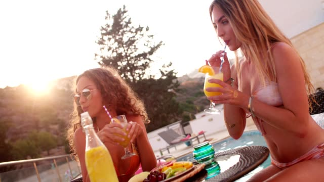 Multi-ethnic female friends in bikinis having breakfast by the pool video