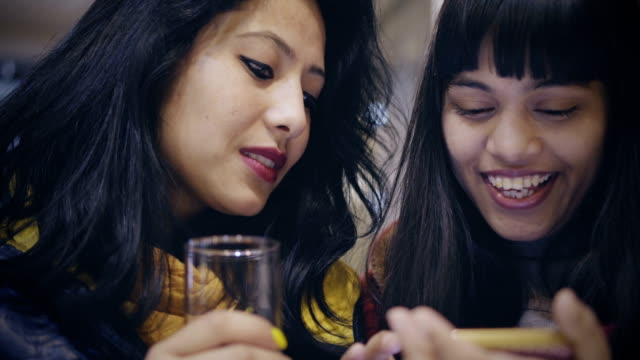 Multi-ethnic female friends sharing smartphone together. video