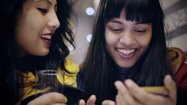 Multi-ethnic female friends sharing smartphone together. Indoor low angle 4k camera dolly video of happy multi ethnic, Asian, Indian young adult female friends sitting in a restaurant and sharing smart phone together. Two people, head-shot and selective focus. close to stock videos & royalty-free footage