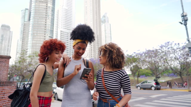 Multi-ethnic female friends standing on sidewalk and checking social media