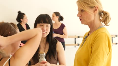 Multi-ethnic females discussing in dance studio Females talking with instructor during break in fitness studio. Multi-ethnic women are discussing at health club. They are in dance class. black hair stock videos & royalty-free footage