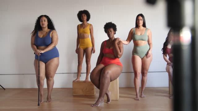 Multi-ethnic females in posing lingerie Group of body positive female models in underwear posing for a photo shoot. Multi-ethnic females in lingerie on studio. plus size model stock videos & royalty-free footage