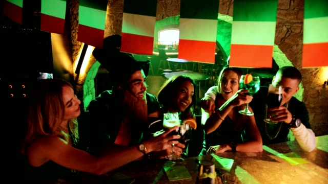 Multi-ethnic friends and couples celebrating Saint Patrick's day at pub video