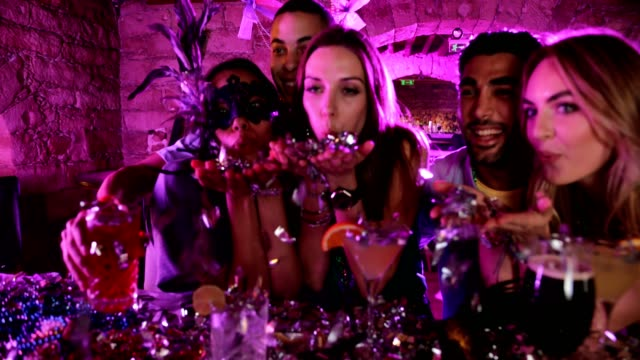 Multi-ethnic friends blowing confetti and celebrating at Mardi Gras party video