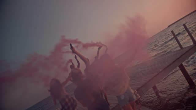 Multi-ethnic friends celebrating with smoke bombs on jetty at sunset Young multi-ethnic hipster friends celebrating and running with smoke bombs on jetty by the sea beach party stock videos & royalty-free footage